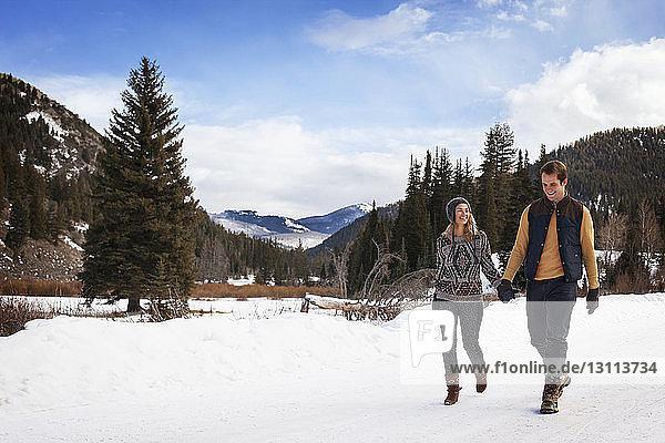 Glückliches Paar hält sich an den Händen  während es auf verschneitem Feld gegen den Himmel läuft