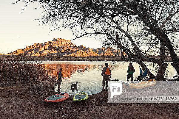 Freunde mit Wassersportgeräten am Seeufer in der Dämmerung