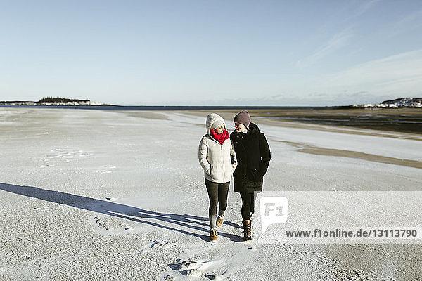 Full length of female friends walking on snowy field against sky during winter