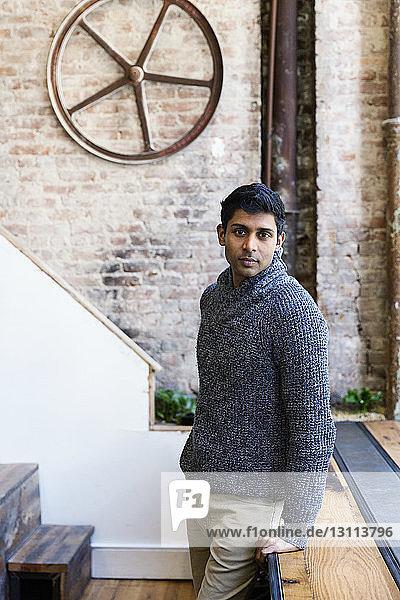 Porträt eines selbstbewussten mittelständischen Geschäftsmannes  der sich im Kreativbüro an den Tisch lehnt