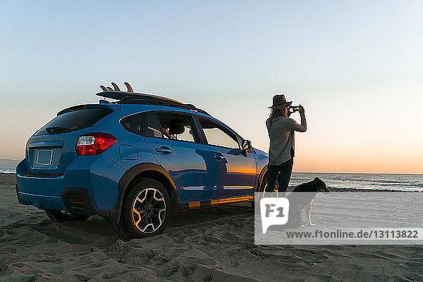 Frau fotografiert stehend mit Hund im Auto am Strand