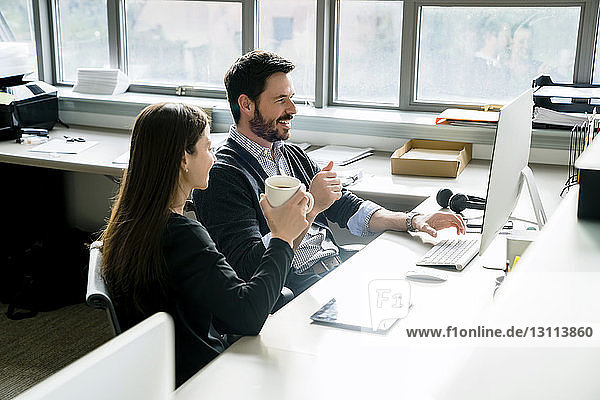 Lächelnder Geschäftsmann am Desktop-Computer  während er mit einer Kollegin im Büro sitzt