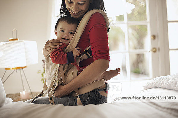 Mother carrying daughter while sitting on bed at home