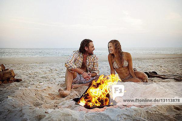 Glückliches Paar unterhält sich am Strand am Lagerfeuer im Sand sitzend