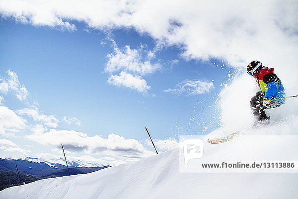 Man skiing on snow against cloudy sky