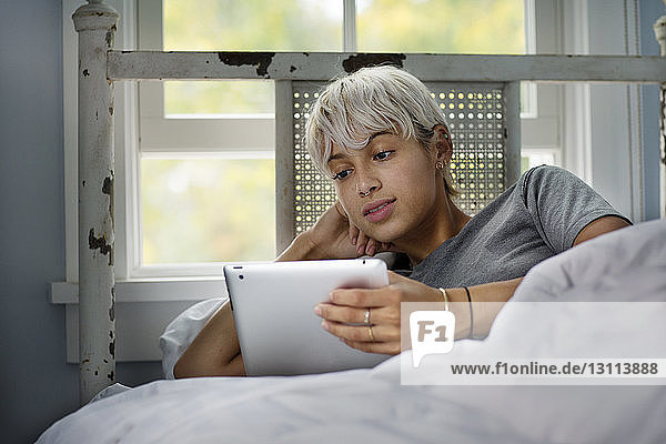 Young woman looking at tablet computer while relaxing on bed