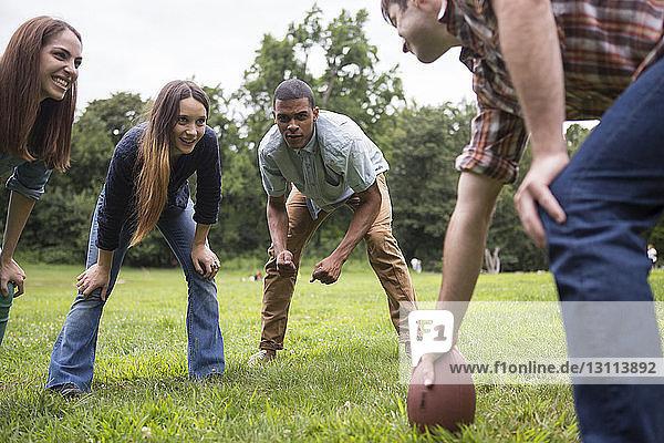 Freunde betrachten Mann mit Fussball in der Hand auf einem Rasenplatz