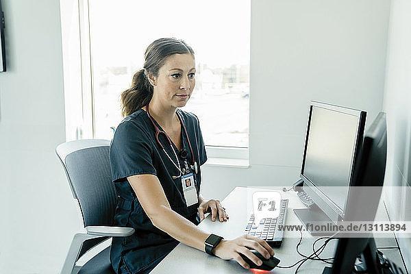 Confident female doctor using desktop computer in hospital