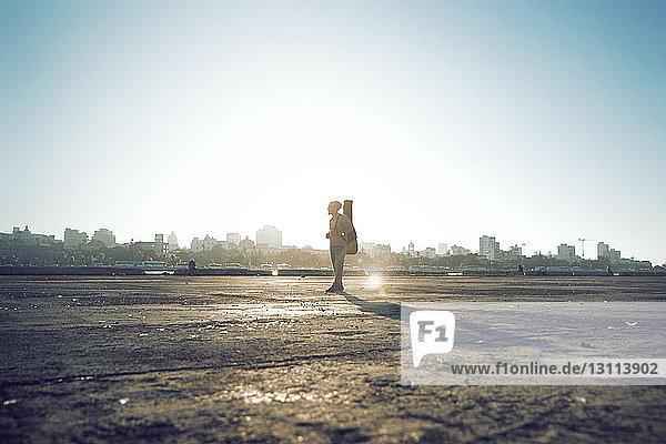 Seitenansicht eines Mannes mit Gitarrenkoffer  der auf dem Feld vor klarem Himmel steht
