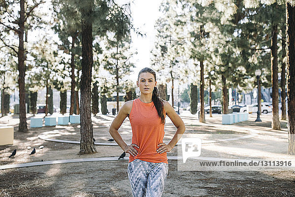 Portrait of confident female athlete standing with hands on hip at park
