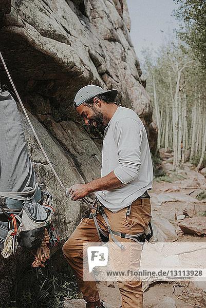Glücklicher Mann bindet Seil vor dem Bergsteigen