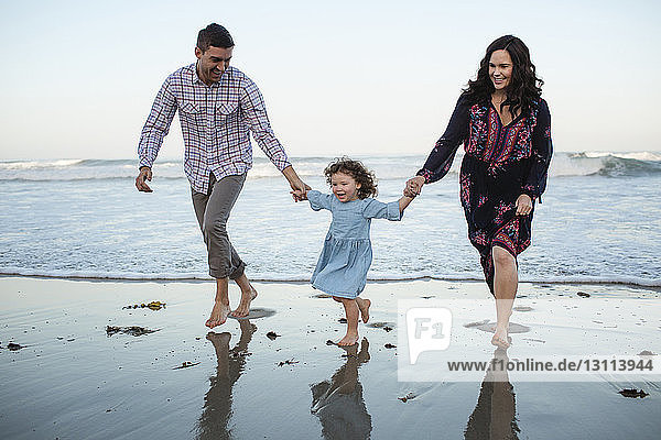 Happy daughter holding hands of parents while walking on shore at beach against clear sky
