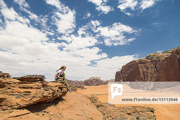Frau sitzt an einem sonnigen Tag auf einem Felsen gegen den Himmel