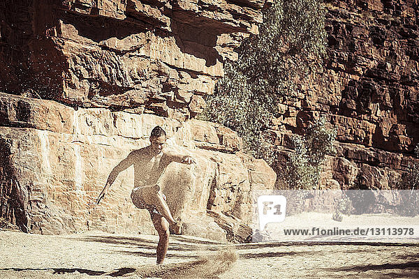 Mann tanzt bei Sonnenschein auf Sand gegen Felsformationen