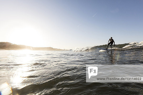 Man surfing on sea against clear sky during sunset