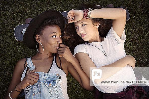 Draufsicht auf Freunde  die sich mit dem Kopf auf einem Skateboard ausruhen  während sie auf einem Grasfeld liegen