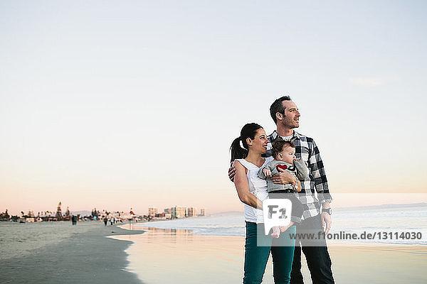 Familie  die bei Sonnenuntergang am Strand am klaren Himmel steht