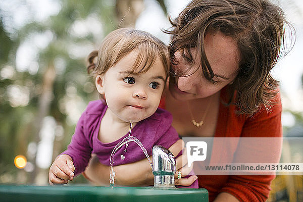 Mother helping cute daughter in drinking water from fountain