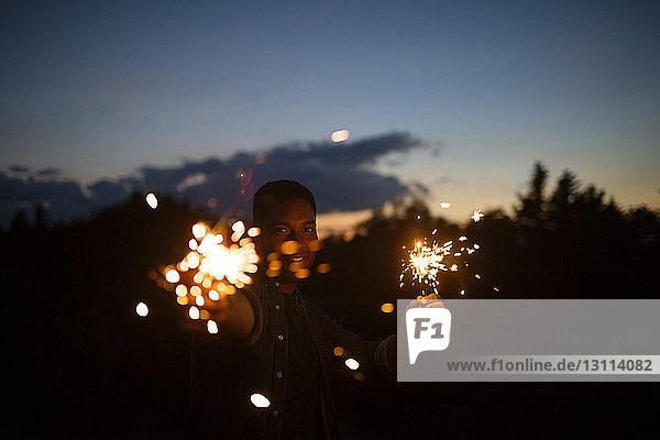 Portrait of man holding sparklers against sky at night