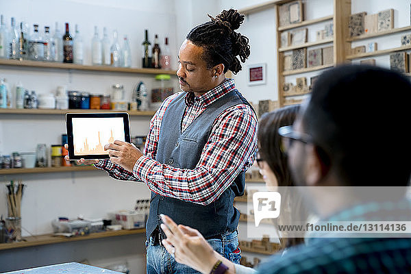 Geschäftsmann zeigt seinen Kollegen im Büro Grafiken auf einem Tablet-PC