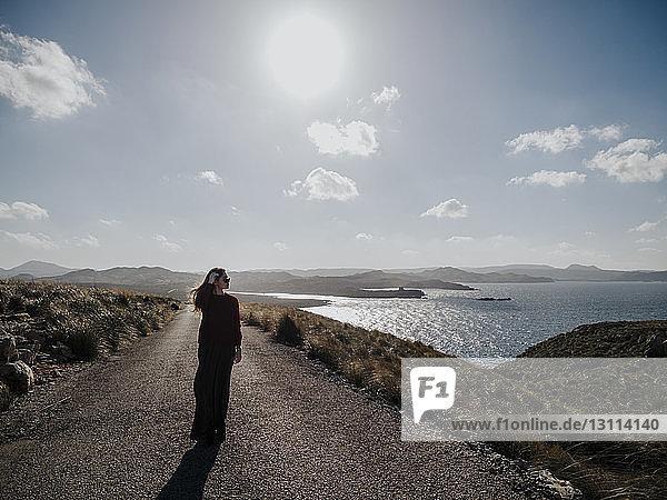 Frau  die am sonnigen Tag auf der Straße am Meer gegen den Himmel läuft