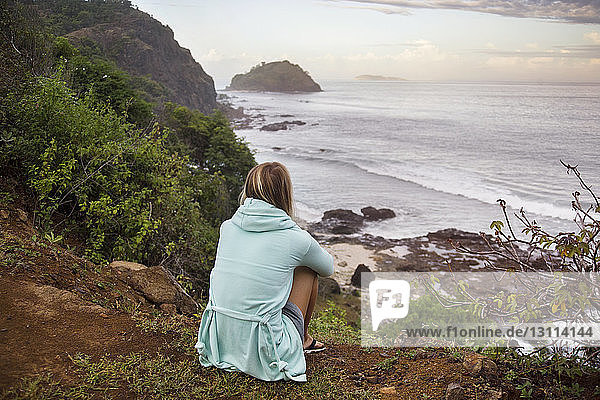 Rear view of woman looking at sea view while sitting on hill