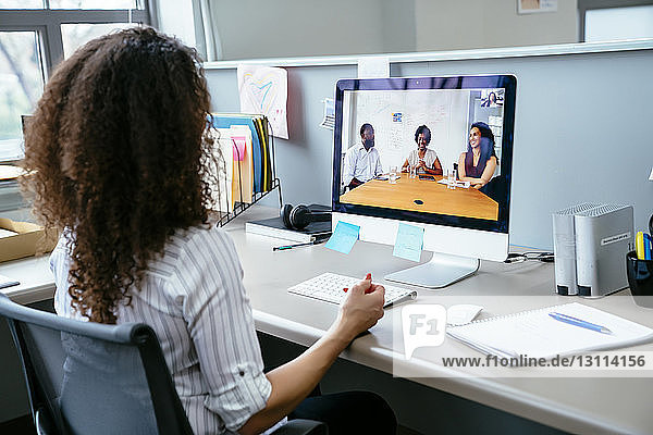 Businesswoman video conferencing with colleagues over desktop computer at desk in office