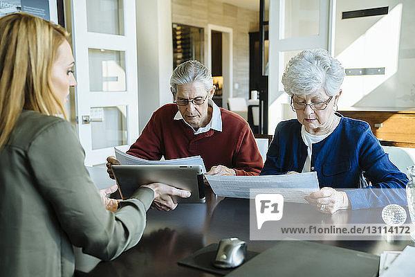 Älteres Ehepaar liest Dokumente im Büro des Finanzberaters