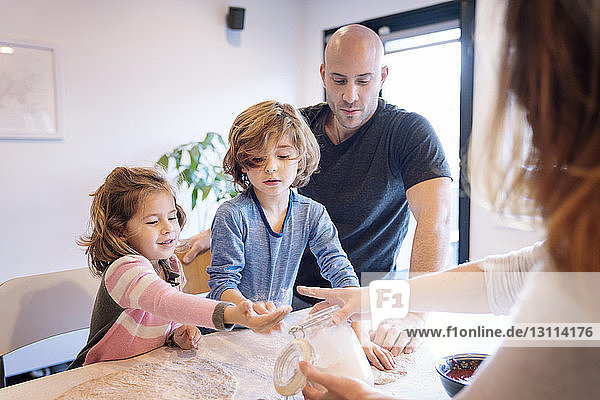 Parents assisting children in kneading dough at table in kitchen