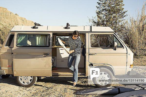 Frau hält Surfbrett in der Hand  während sie im Urlaub aus dem Kleinbus steigt