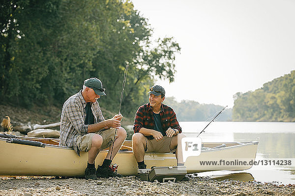 Friends with fishing rods talking while sitting on boat at lakeshore