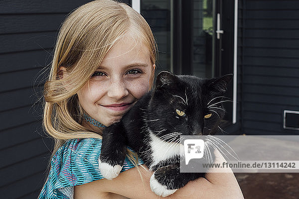 Nahaufnahme eines Mädchens mit Katze  das vor dem Haus steht