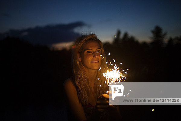 Portrait of smiling woman holding sparklers at night
