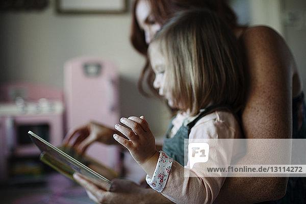 Seitenansicht von Mutter und Tochter mit Bilderbuch zu Hause