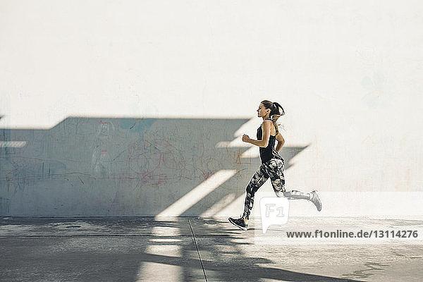 Full length side view of female athlete running on sidewalk against white wall