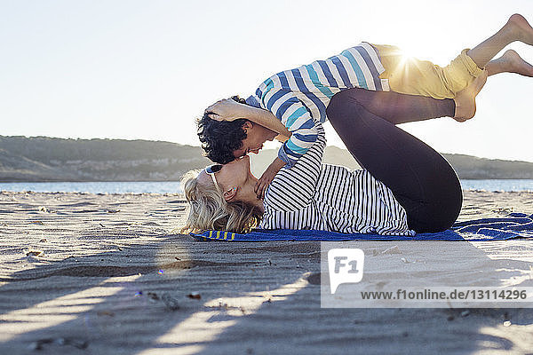 Side view of loving mother kissing son while lying on beach