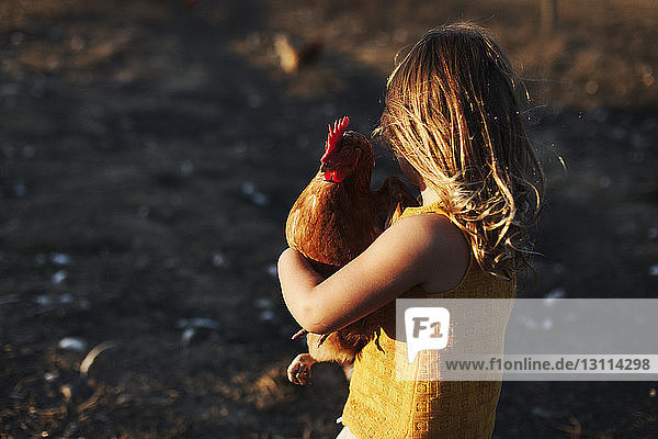 Side view of girl carrying hen while standing on field