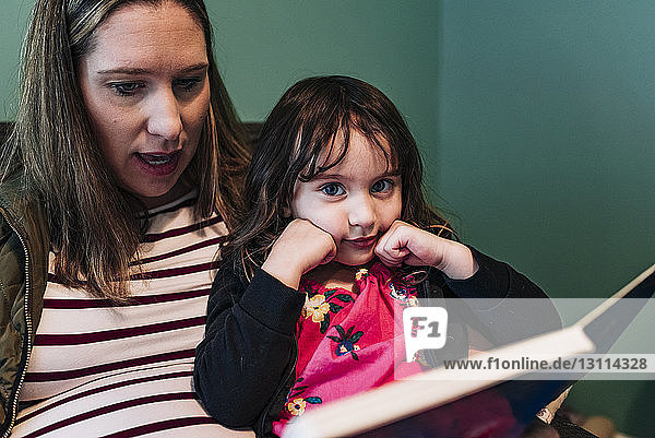Pregnant mother with daughter reading book while sitting at home