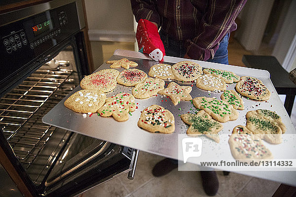 Senior man holding gingerbread cookies in baking sheet at home