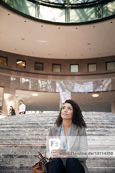 Nachdenkliche Geschäftsfrau hält Smartphone und Einwegglas in der Hand  während sie auf Stufen sitzt