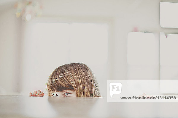 Portrait of girl peeking over table at home