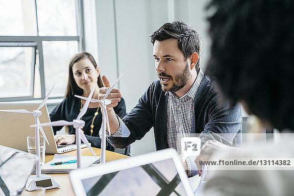 Geschäftsmann erklärt Kollegen im Büro Modelle von Windkraftanlagen
