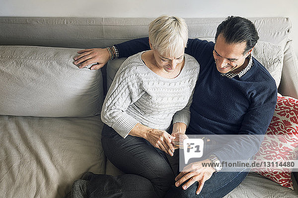High angle view of senior couple looking at smart phone while sitting on sofa at home