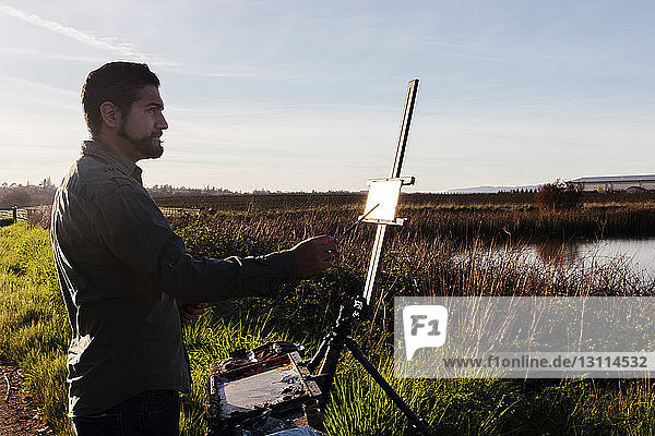 Side view of painter painting on canvas at field against sky