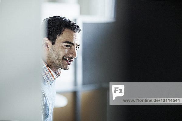 Lächelnder Geschäftsmann durch eine Tür im Büro gesehen