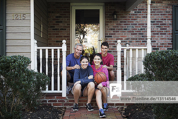 Portrait of happy family sitting on front stoop outside house