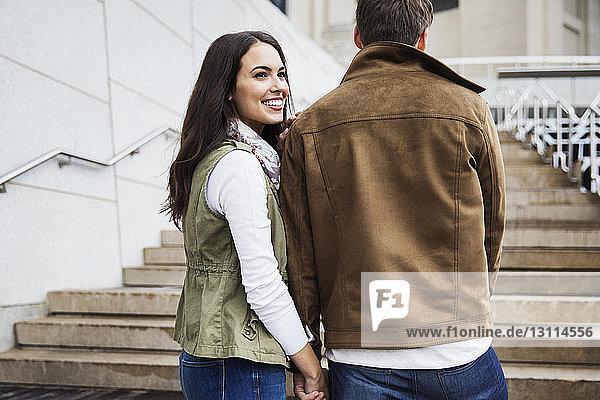 Glückliche Frau schaut weg  während sie mit ihrem Freund die Treppe hinaufgeht