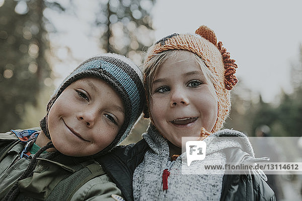Portrait of smiling brothers wearing knit hats at Yosemite National Park