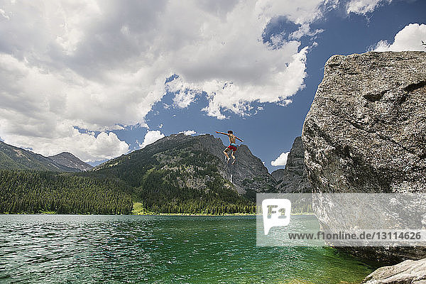 Teenager boy cliff jumping in lake against cloudy sky