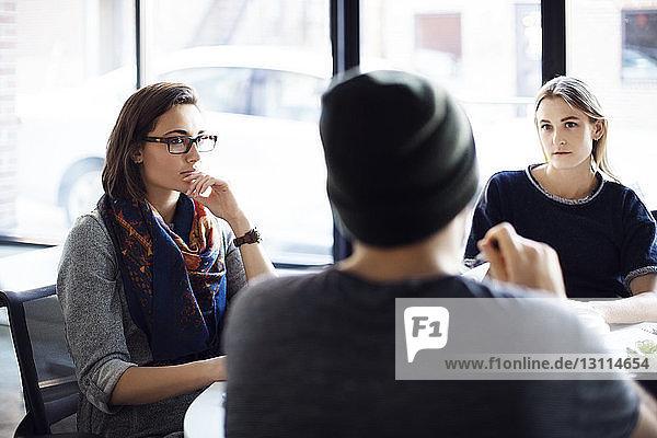 Weibliche Kollegen  die einem Geschäftsmann während einer Besprechung im Büro zuhören